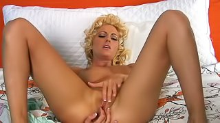Cody Love with curly blond hair and shaved pussy loves to play with herself in the bedroom. She takes off her see-through underwear and then masturbates with her legs apart