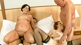 Margo T and Eodit are two horny grannies that get their mouths and dripping wet pussies fucked side by side. Two fuck hungry oldies do it on a king size bed in steamy foursome action!