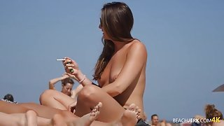 Cigarette smoking beach chick with her tits out